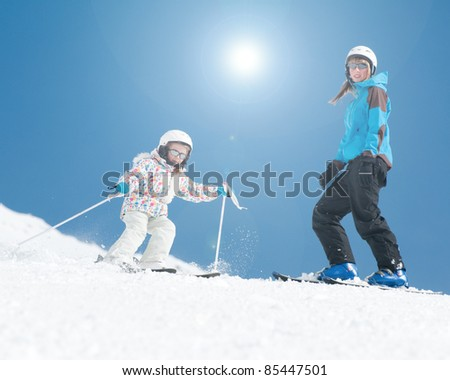 Skiing - young skiers skiing downhill - stock photo