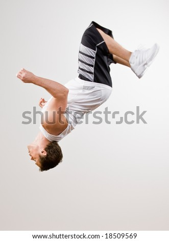 Skilled athlete in sportswear doing somersault in mid-air - stock photo