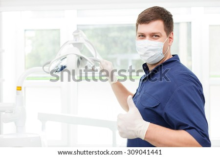Skilled attractive dental doctor is touching medical technique and giving thumb up. He is looking forward with happiness. He is wearing a mask and gloves - stock photo