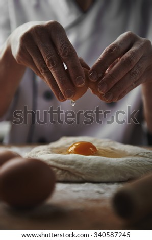 Skilled baker preparing dough for pasta, pizza or pie. Woman chef breaking egg into dough.  - stock photo