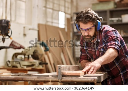 Skilled carpenter cutting a piece of wood in his woodwork workshop, using a circular saw, and wearing safety googles and earmuffs, with other machinery in the background - stock photo