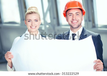 Skilled engineers are discussing a new project. They are holding s blueprint and smiling. The man and woman are standing and looking at the camera happily - stock photo