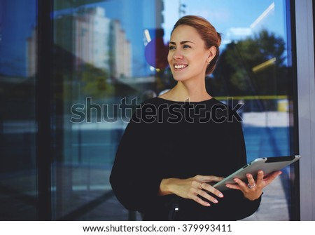 Skilled female manager hold digital tablet and smiling to someone during rest after conference, Successful smiling woman entrepreneur distracted from work on touch pad standing near company's building - stock photo