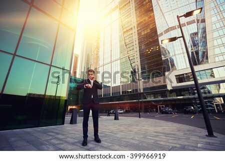 Skilled man managing director of prosperous company is checking time and talking on mobile phone, while is standing outside near skyscrapers. Successful male CEO having cell telephone conversation