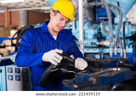 skilled man working in a gumboot factory - stock photo