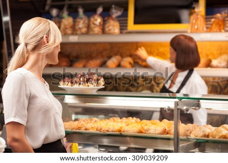 Skilled saleswoman is serving her customer in bakery. She is taking pastry from the shelf with joy. The blond woman is looking at sweet food with temptation and smiling - stock photo