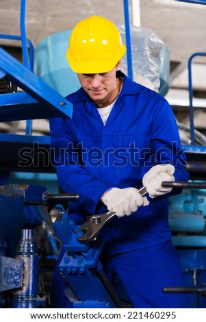 skilled young mechanic repairing factory machine - stock photo