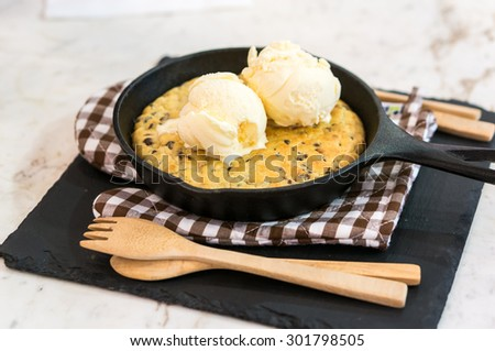 Skillet Cookies with Vanilla Ice Cream and Wood Spoon and Fork on Gloves - stock photo