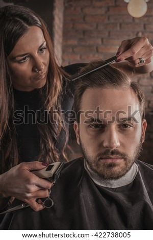 Skillful female hairdresser hairstyle hair of attractive man in hair salon - stock photo
