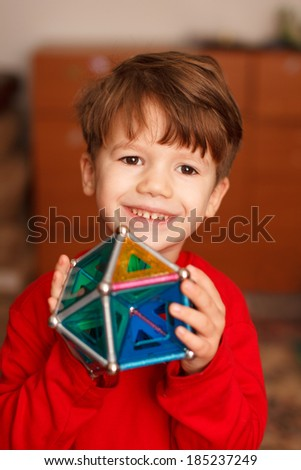 Skillful little boy holding toy, teeth smile, indoor portrait - stock photo