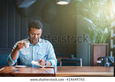 Skillful male worker is drinking hot beverage - stock photo