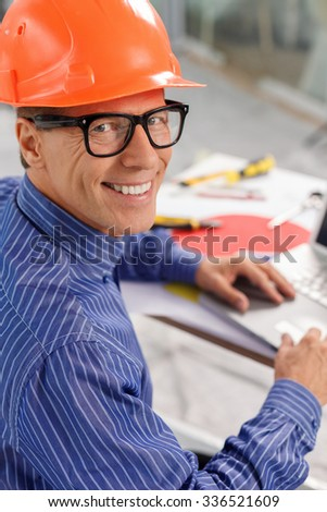 Skillful mature engineer is projecting the building. He is typing on the laptop and smiling. The man is sitting at the table and looking forward happily