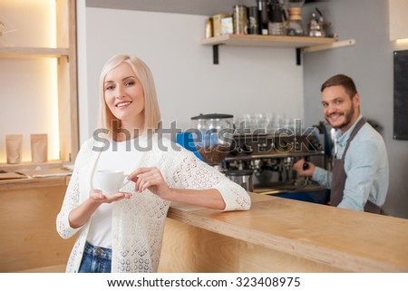 Skillful young barista is making coffee for the client in cafe. The man is standing near equipment with joy. The woman is leaning on the counter and drinking a cup of coffee. They are smiling