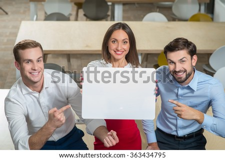 Skillful young working team is presenting white empty placard. The businesswoman is standing and holding billboard. The businessmen are sitting and pointing finger at it. They are smiling - stock photo