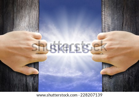 Skills word floating and shining in the sky while two hands opening an old wooden door. - stock photo