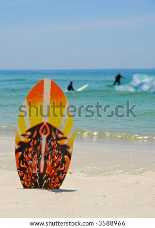 Skim Board with Surfers in Background - stock photo