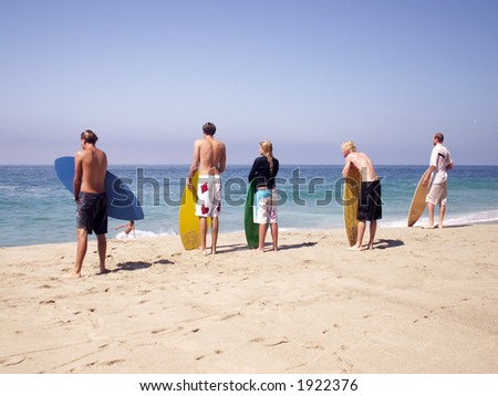Skimmers waiting for the right shore break to surf. - stock photo