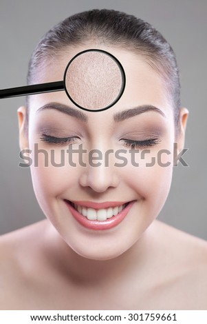 Skin care and beauty concept - face of beautiful young woman with smile over gray background. skin defect on face by loupe. closed eyes looking at camera. - stock photo