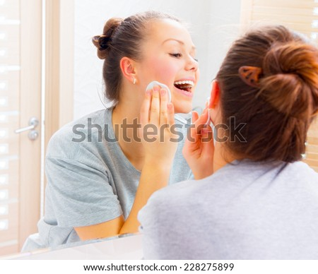 Skin care. Beauty teenager girl cleaning her face with cotton pad at home. Young happy brunette woman removing makeup from her face enjoying her skin and smiling at the mirror. Skincare, cleansing  - stock photo