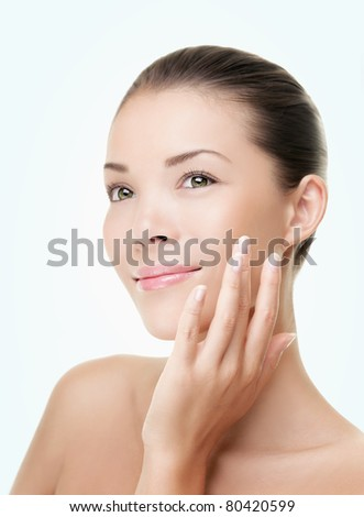 Skin care beauty woman. Beauty woman smiling applying cream. Beauty portrait of beautiful Asian / Caucasian female model isolated on light blue background looking at copy space. - stock photo