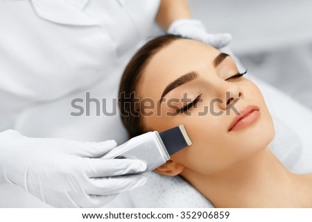 Skin Care. Close-up Of Beautiful Woman Receiving Ultrasound Cavitation Facial Peeling. Ultrasonic Skin Cleansing Procedure. Beauty Treatment. Cosmetology. Beauty Spa Salon. - stock photo