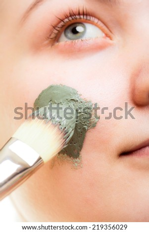 Skin care. Closeup of woman applying with brush clay mud mask on face. Girl taking care of dry complexion. Beauty treatment. - stock photo