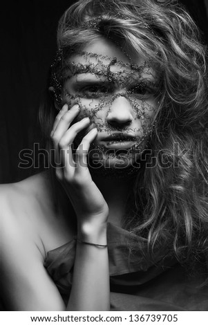 Skin care concept. Nightmare of a young glamorous blonde woman in gray cloth. Wire mask on a face. Studio shot - stock photo