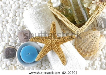 skin care items with starfish and sea shells on white pebble - stock photo