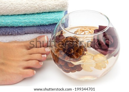 Skin care of a beauty female feet with flowers and cone - stock photo