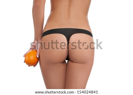 Skin care. Rear view of woman holding orange near her buttocks while isolated on white
