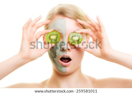Skin care. Surprised woman in clay mud mask on face covering eyes with slices of kiwi isolated. Girl taking care of dry complexion. - stock photo