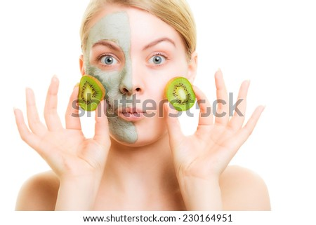 Skin care. Surprised woman in clay mud mask on face holding slices of kiwi fruit isolated. Girl taking care of dry complexion. - stock photo