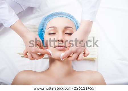 Skin care - woman cleaning face by beautician over white background - stock photo