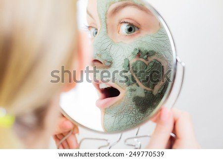 Skin care. Woman in clay mud mask on face with heart symbol of love on cheek looking in the mirror. Girl taking care of dry complexion. - stock photo