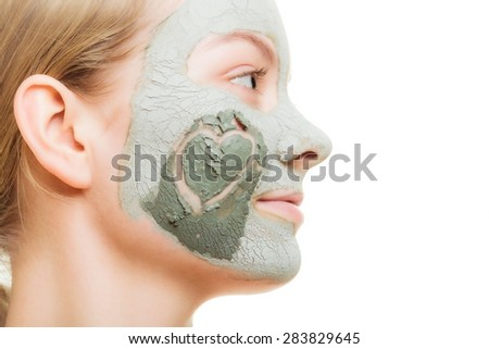 Skin care. Woman in clay mud mask with heart symbol of love on cheek isolated on white. Girl taking care of dry complexion. Beauty treatment. - stock photo