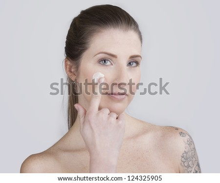 Skin care woman putting face cream touching under eyes. Facial beauty closeup of beautiful mixed race Asian / Caucasian female model isolated on white background.