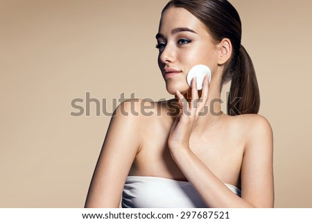 Skin care woman removing face makeup - skin care concept / photos of appealing brunette girl on beige background - stock photo