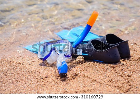 Skin diving equipment standing ready on a beach on the sand at the edge of the sea with a pair of flippers, snorkel and goggles, conceptual of recreational activities on summer vacation - stock photo