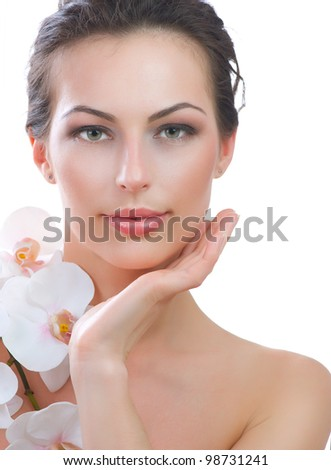 Skincare.Beautiful Young Woman Face With Fresh Flower on a White Background - stock photo