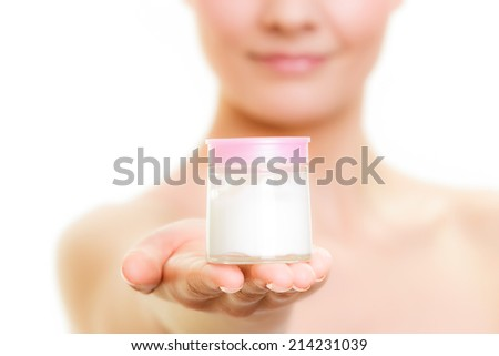 Skincare. Closeup of woman holding lotion jar. Blond girl taking care of her dry complexion applying moisturizing cream isolated. Beauty treatment. - stock photo