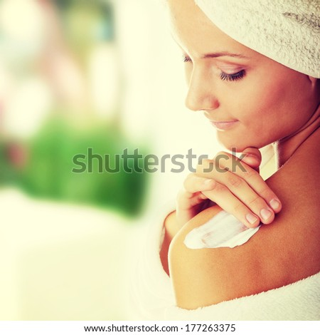 Skincare concept: back of beautiful nude woman with soft skin putting skincare product (cream) on her back  - stock photo