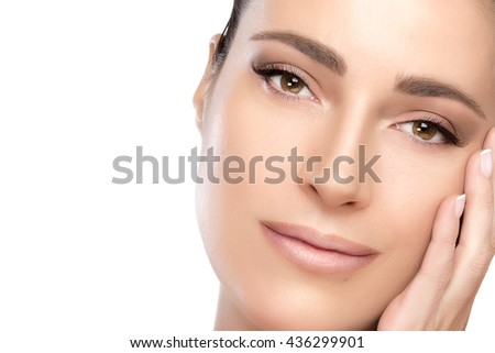 Skincare concept. Beauty portrait of a gorgeous serene woman with flawless skin and her hand to her cheek isolated on white in a close up cropped view with copy space - stock photo
