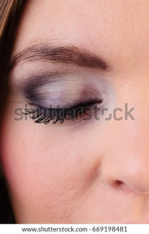 Skincare cosmetics and make up. Young woman with eyeshadows and mascara closeup portrait closed eyes