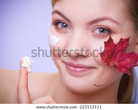 Skincare habits. Face of young woman with leaf as symbol of red capillary skin on gray. Girl taking care of her dry complexion applying moisturizing cream. Beauty treatment.