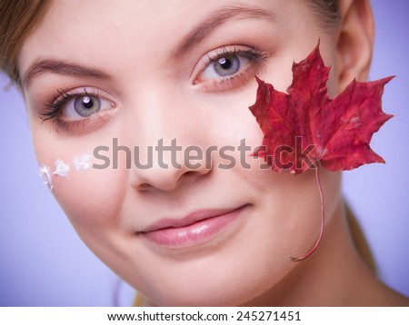 Skincare habits. Face of young woman with leaf as symbol of red capillary skin on gray. Girl taking care of her dry complexion applying moisturizing cream. Beauty treatment. - stock photo