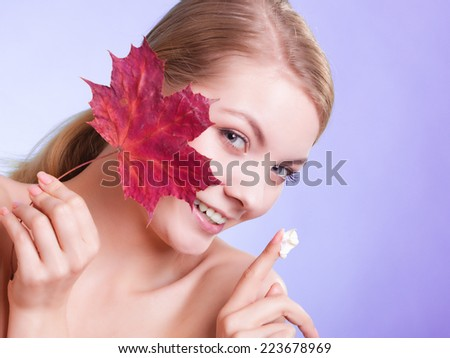 Skincare habits. Face of young woman with leaf as symbol of red capillary skin on violet. Girl taking care of her dry complexion applying moisturizing cream. Beauty treatment. - stock photo
