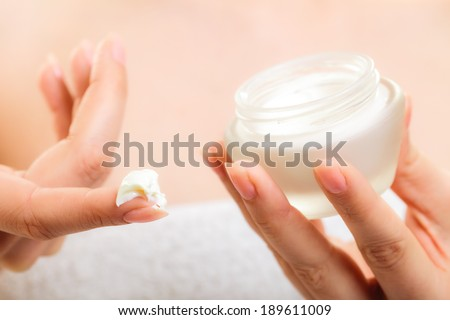 Skincare. Woman taking care of her dry complexion. Moisturizing cream in female hands isolated. Beauty treatment. - stock photo