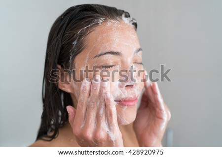 Skincare woman washing face in shower foaming facewash soap scrub on skin. Asian female adult cleaning body showering in hot water at home on in hotel as morning routine. Enjoying relaxing time. - stock photo