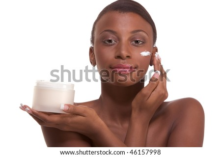 Skincare - Young naked ethnic African-American woman with slicked back hair applying cream moisturizer on her face after sauna - stock photo