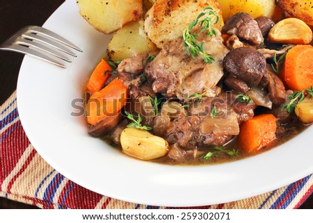 Skinless, boneless chicken thighs braised in red wine - stock photo